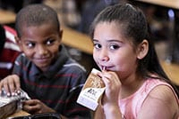 Two students, a boy and a girl; the girl looks at the camera while drinking chocolate milk.